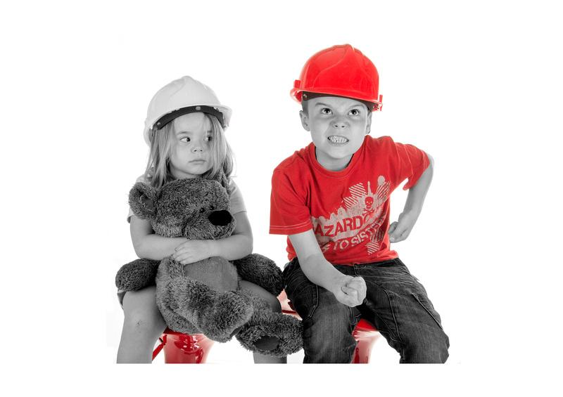 Studio portrait of a boy and girl wearing hard hats